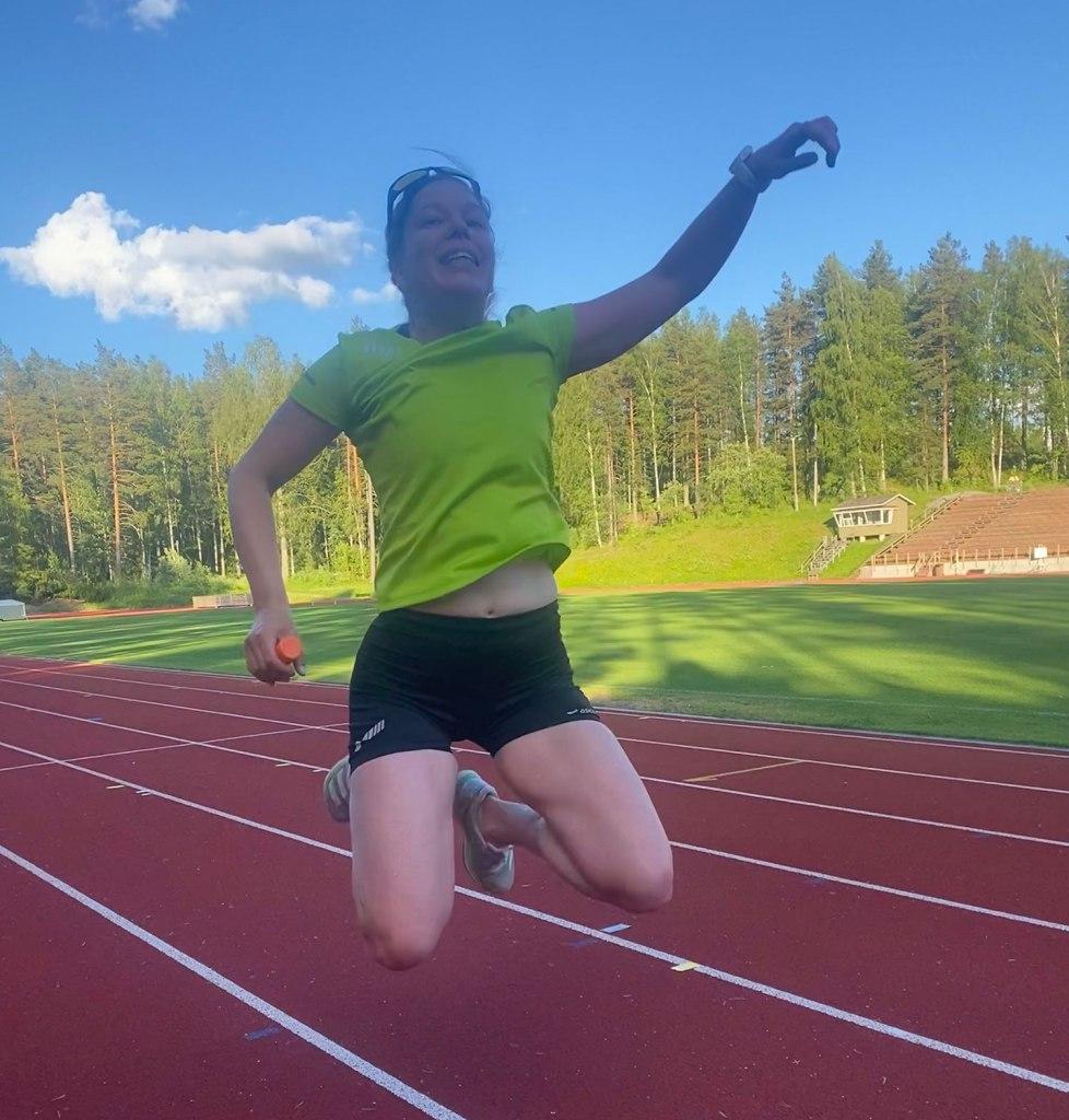 Juoksija hyppää ilmaan urheilukentällä.