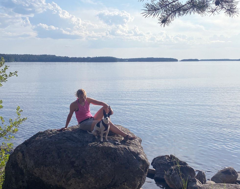 nainen ja koira istuvat kivellä Saimaan rannalla