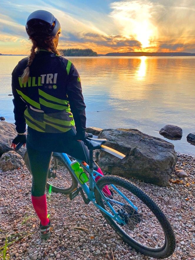 Maastopyöräilijä katselee Saimaaseen laskevaa aurinkoa
